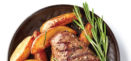 Grilled beef and potatoes with garnish.