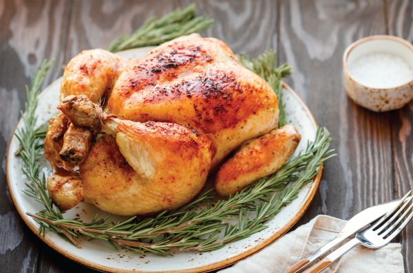Whole baked chicken on bed of rosemary
